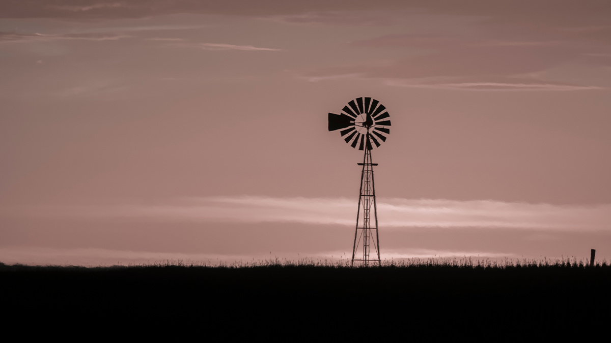 Windmill in countryside at sunset